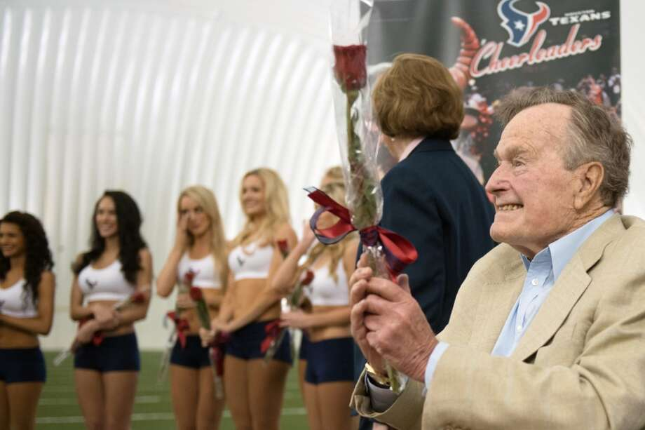 Former President George H.W. Bush presents newly announced Houston Texans cheerleaders with a rose during a ceremony announcing the new squad,