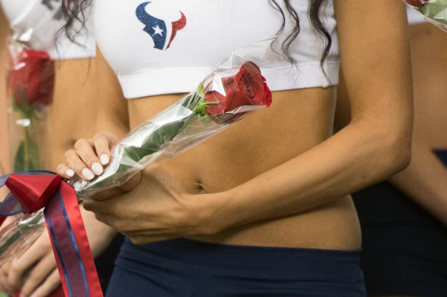 A new Houston Texans cheerleader holds a rose presented to her by former President George H.W. Bush,