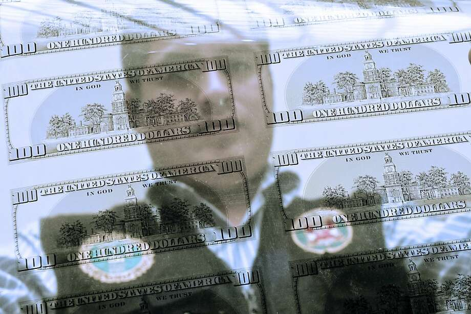 A policeman is reflected in a photolith used to print sheets of 100 US Dollars counterfeit bills seized by the Department of Criminology (Dirincri) during a presentation to the press in Lima on April 17, 2013. About 15 Millions dollars was seized by the Peruvian Police, from a criminal organization dedicated to make counterfeit dollar to be sent to the United States, Europe and others countries in the region.  AFP PHOTO/ERNESTO BENAVIDESERNESTO BENAVIDES/AFP/Getty Images Photo: Ernesto Benavides, AFP/Getty Images