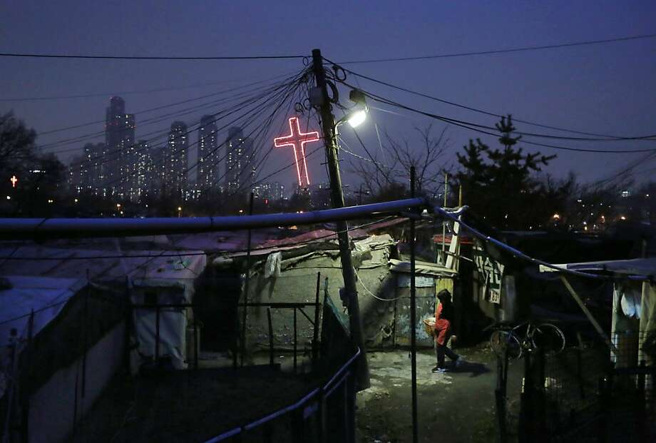 A resident walks beside a church at Guryong Village with a backdrop of high-rise buildings of Seoul's wealthiest Gangnam district, left, in Seoul, South Korea, Tuesday, April 16, 2013. (AP Photo/Kin Cheung) Photo: Kin Cheung, Associated Press