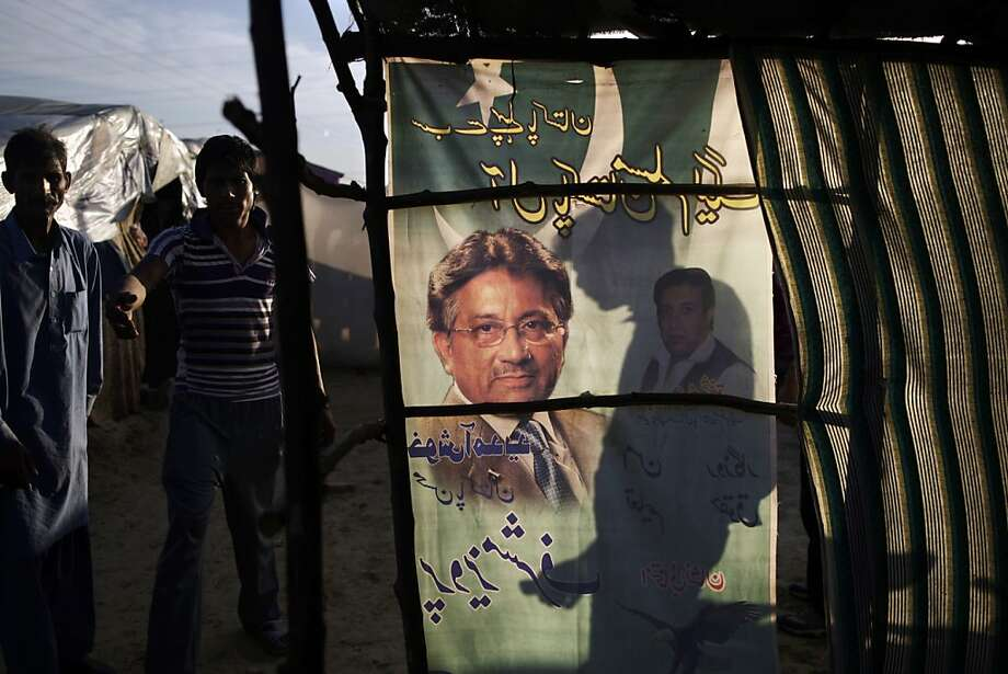 An election banner showing Pakistan's former president and military ruler Pervez Musharraf, is used as a curtain on a makeshift home in a Christian slum on the outskirts of Islamabad, Pakistan, Wednesday, April 17, 2013. Musharraf appeared in court to seek bail in Benazir Bhutto's assassination case. Pakistan's Supreme Court ordered Musharraf to respond to allegations that he committed treason while in power, and barred him from leaving the country only weeks after he returned. (AP Photo/Muhammed Muheisen) Photo: Muhammed Muheisen, Associated Press