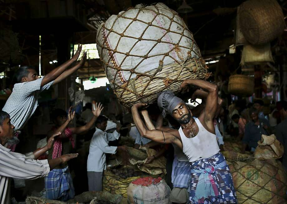Indian laborers drop a large heavy bundle of vegetables in front of a vendors stall at a wholesale vegetable market in Kolkata, eastern India, Wednesday, April 17, 2013. (AP Photo/Kevin Frayer) Photo: Kevin Frayer, Associated Press