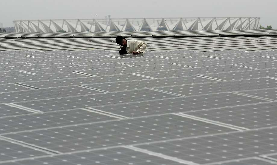 (FILES) In this photogrpah taken on September 1, 2010, the national Jawaharlal Nehru Stadium looms in the background as an Indian worker cleans solar panels on top of the newly-built Thyagraj Stadium in New Delhi. India's prime minister urged global companies on April 17, 2013 to make the sun-baked South Asian nation a solar energy hub as the country seeks to cut its chronic power shortages. AFP PHOTO/MANAN VATSYAYANA/FILESMANAN VATSYAYANA/AFP/Getty Images Photo: Manan Vatsyayana, AFP/Getty Images