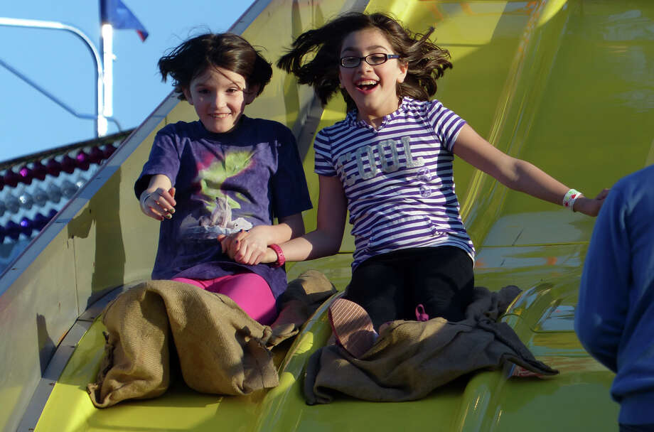 Abigail Agostin, 9, left, and her friend Paula Ardissone, 9, ride the slide at the  Trumbull Rotary Club Carnival at Hillcrest Middle School in Trumbull, Conn. on Wednesday April 17, 2013. The carnival continues through Sunday April 21st. This year, money raised will go towards building a home in Bridgeport for a vet's family through the work by the Trumbull Rotary Club and Habitat for Heroes. More information can be found at www.trumbullrotary.org and www.habitatcfc.org. Photo: Christian Abraham / Connecticut Post