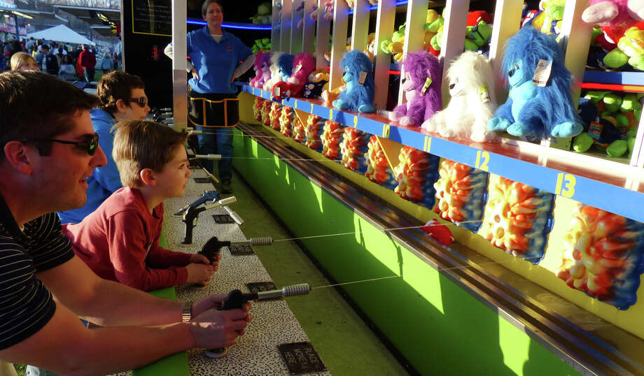 Andrew Duncan and his son Brody, 5, play one of the games at the Trumbull Rotary Club Carnival at Hillcrest Middle School in Trumbull, Conn. on Wednesday April 17, 2013. The carnival continues through Sunday April 21st. This year, money raised will go towards building a home in Bridgeport for a vet's family through the work by the Trumbull Rotary Club and Habitat for Heroes. More information can be found at www.trumbullrotary.org and www.habitatcfc.org. Photo: Christian Abraham / Connecticut Post