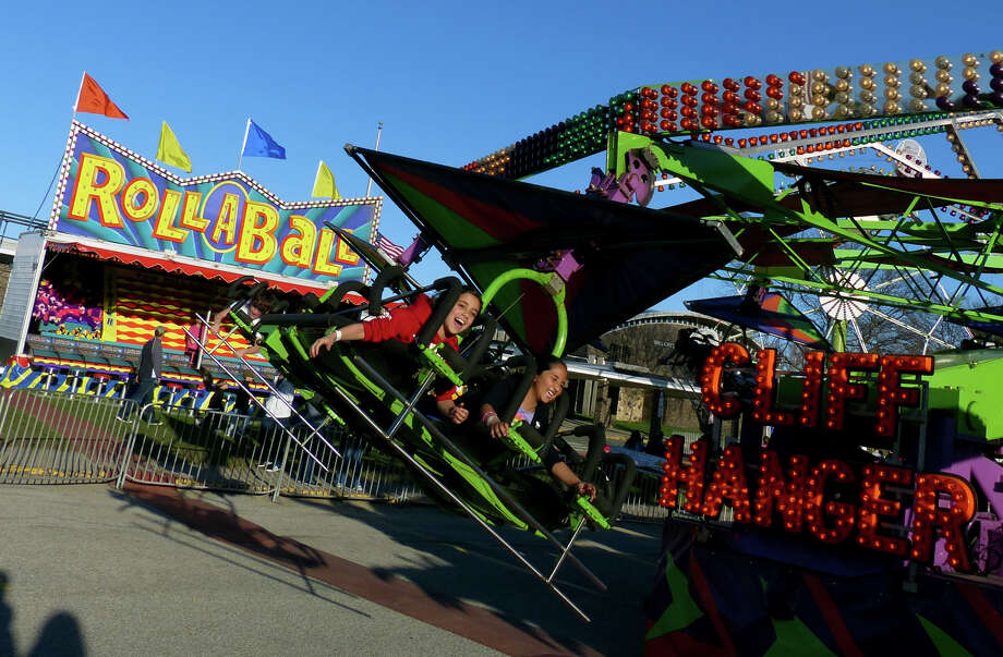 Marcella Cecere, 8, left, and her friend Gia Barhpaga, 8, take a ride on the Cliff Hanger, during the Trumbull Rotary Club Carnival at Hillcrest Middle School in Trumbull, Conn. on Wednesday April 17, 2013. The carnival continues through Sunday April 21st. This year, money raised will go towards building a home in Bridgeport for a vet's family through the work by the Trumbull Rotary Club and Habitat for Heroes. More information can be found at www.trumbullrotary.org and www.habitatcfc.org. Photo: Christian Abraham / Connecticut Post