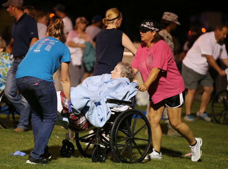 An elderly person is assisted at a staging area at a local school stadium  following an explosion at