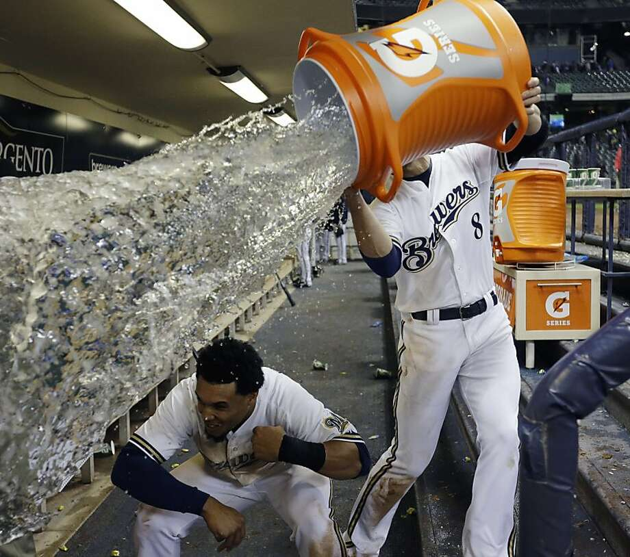 Milwaukee Brewers' Carlos Gomez ducks out of the way as teammate Ryan Braun (8) tries to dunk him with water after a baseball game against the San Francisco Giants Wednesday, April 17, 2013, in Milwaukee. The Brewers won 4-3. (AP Photo/Morry Gash) Photo: Morry Gash, Associated Press