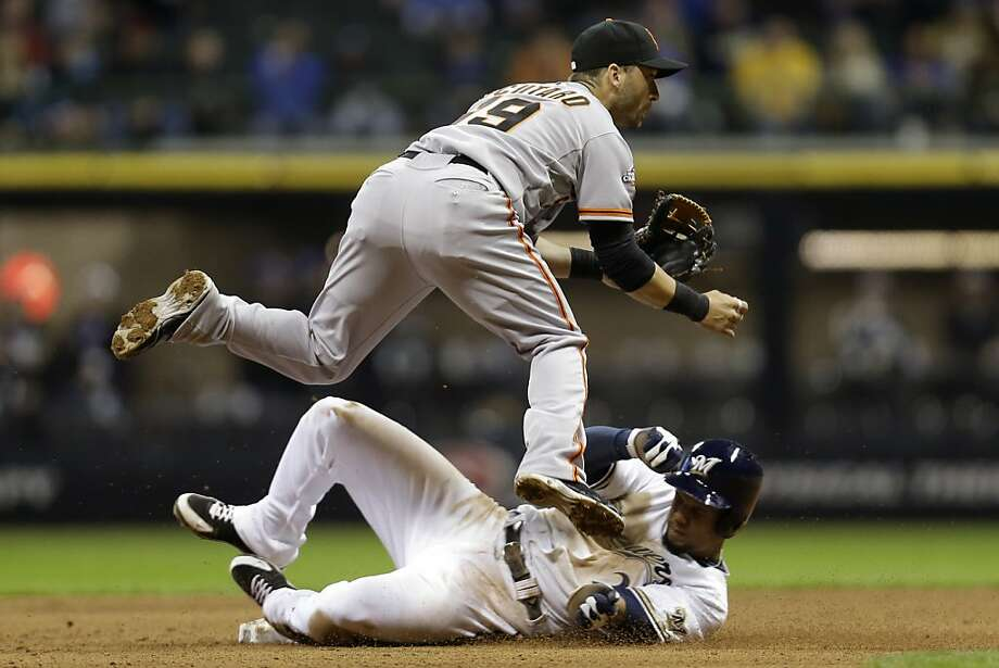 MILWAUKEE, WI - APRIL 17: Marco Scutaro #19 of the San Francisco Giants turns the double play as Carlos Gomez #27 slides into second base during the bottom of the seventh inning against the Milwaukee Brewers at Miller Park on April 17, 2013 in Milwaukee, Wisconsin. (Photo by Mike McGinnis/Getty Images) Photo: Vincent Pugliese, Getty Images