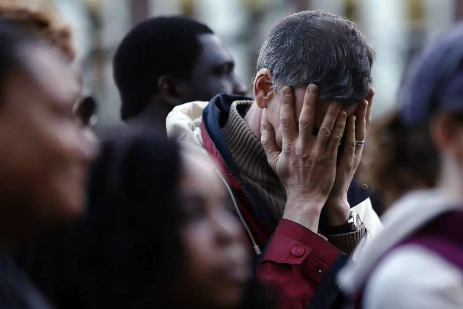 A mourner reacts during a candlelight vigil in the aftermath of Monday's Boston Marathon explosions, which killed at least three and injured more than 140, Wednesday, April 17, 2013, at City Hall in Cambridge, Mass. (AP Photo/Matt Rourke) Photo: Matt Rourke, Associated Press