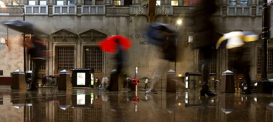 In a time delayed exposure, commuters are blurred as they make their way through strong winds and rain in Chicago, Wednesday, April 17, 2013. Thunder storms, flooding and roller coaster temperatures are plaguing the Chicago area as winter tries to hold on in mid April. (AP Photo/Charles Rex Arbogast) Photo: Charles Rex Arbogast, Associated Press