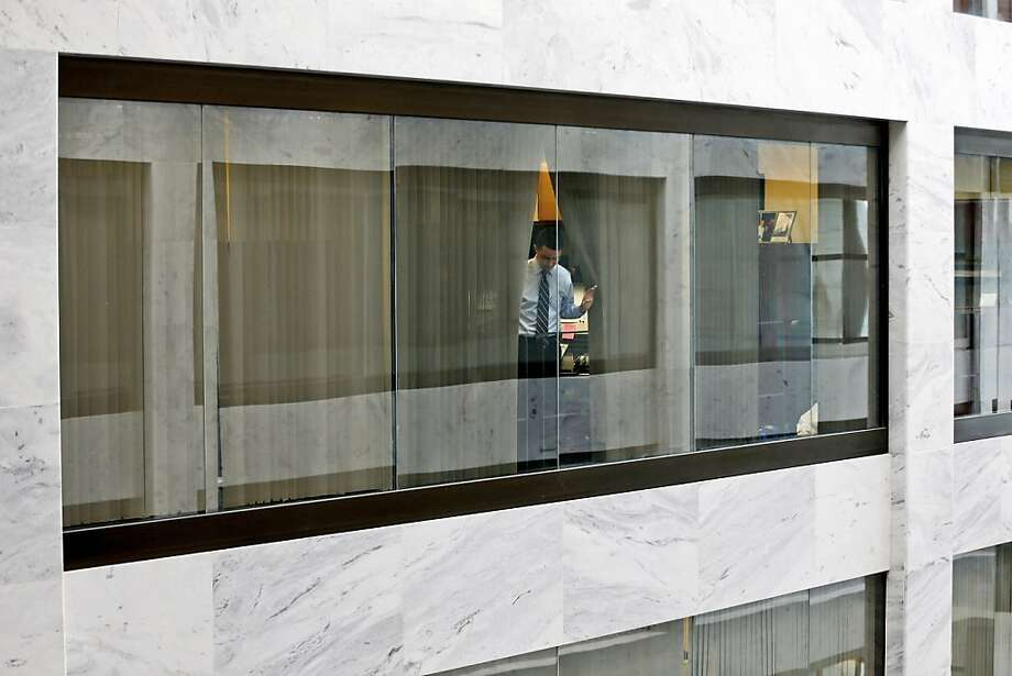 An unidentified staff member looks out from his office window down into the atrium of the Hart Senate Office Building on Capitol Hill in Washington, Wednesday, April 17, 2013, after they were told to shelter in place after reports of suspicious packages discovered on Capitol Hill. U.S. Capitol police are investigating the discovery of at least two suspicious envelopes in Senate office buildings across the street from the Capitol. (AP Photo/Charles Dharapak) Photo: Charles Dharapak, Associated Press