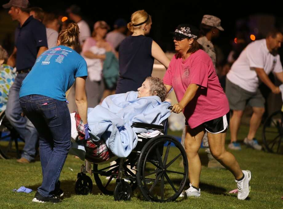 An elderly person is assisted at a staging area at a local school stadium (AP Photo/ Waco Tribune Herald, Rod Aydelotte).
