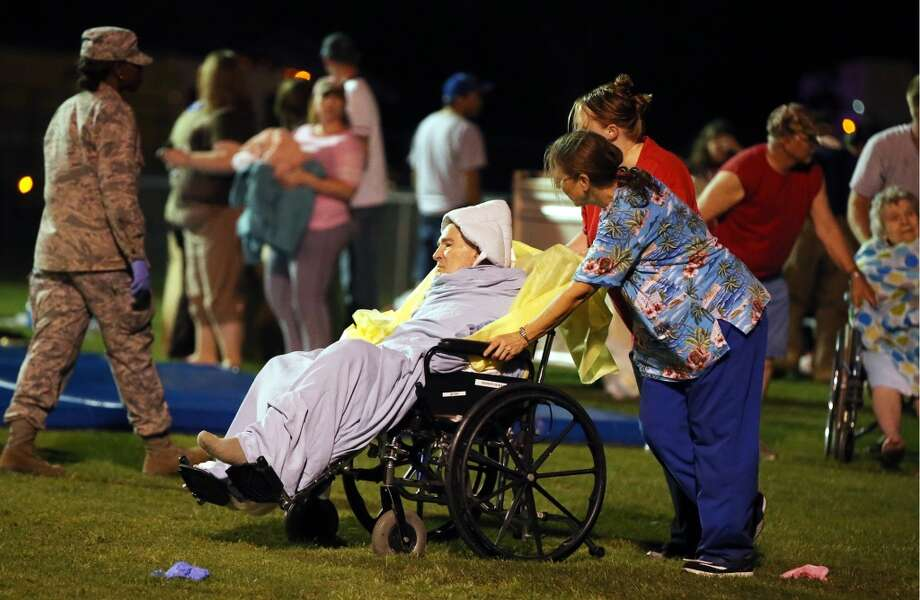 Emergency workers assist an elderly person at a staging area at a local school stadium (AP Photo/Waco Tribune Herald, Rod Aydelotte).