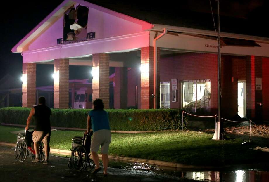People are seen pushing wheelchairs in front of a damaged nursing home. (AP Photo/ Waco Tribune Herald, Rod Aydelotte)