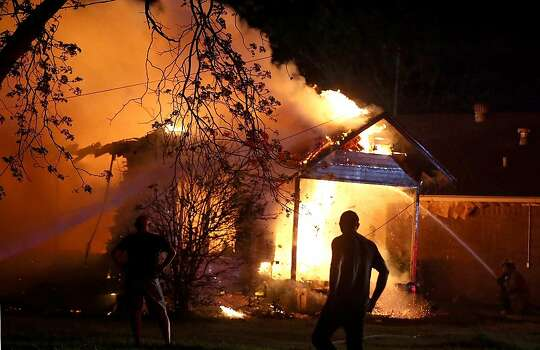 A person looks on as emergency workers fight a house fire after a near by fertilizer plant exploded Wednesday, April 17, 2013, in West, Texas. (AP Photo/ Waco Tribune Herald, Rod Aydelotte) Photo: Rod Aydelotte, Associated Press