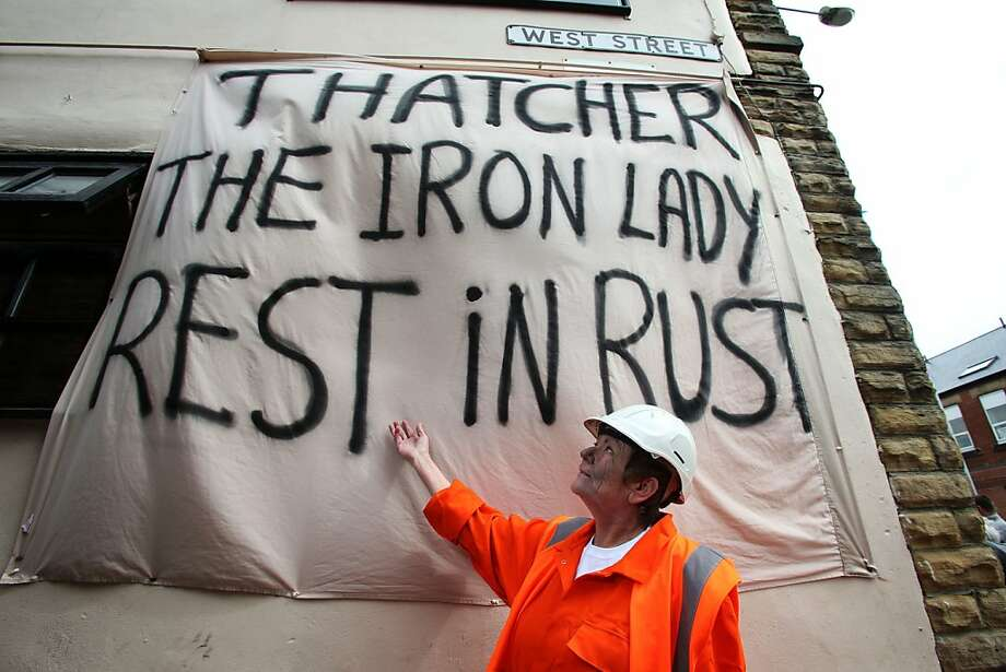 A woman dressed in miners garb in Goldthorpe, northern England as people gather and march to celebrate the  funeral of Baroness Thatcher in London Wednesday April 17, 2013. The death of Britain's first female Prime Minister has deeply split the nation between those who look back on her with respect and those who, like the coal miners with whom she had a bruising confrontation, deeply despised her. The divisive leader ruled the country for 11 years breaking the strength of the trade unions, securing victory in a distant war for the Falkland Islands, and selling off state-owned utilities at a record pace.(AP Photo / Lynne Cameron, PA) UNITED KINGDOM OUT  NO SALES  NO ARCHIVE Photo: Lynne Cameron, Associated Press