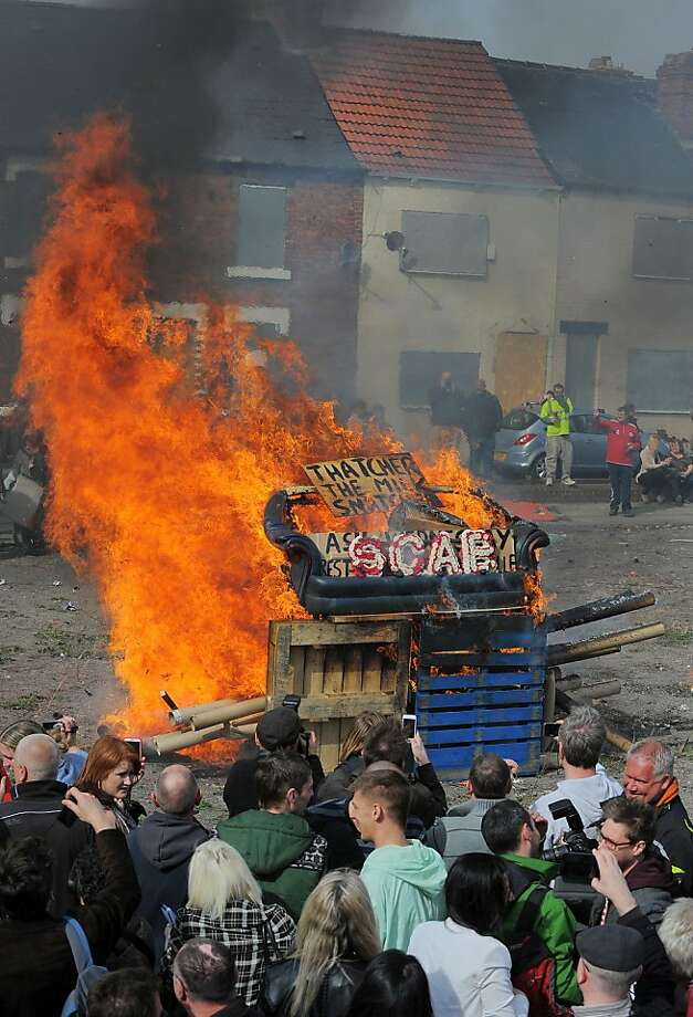 An effigy of former British prime minister Margaret Thatcher in a 'coffin' is burnt together with a sofa and wood as people gather to celebrate the death of Margaret Thatcher in Goldthorpe, northen England, on April 17, 2013. The funeral of Margaret Thatcher took place on April 17, with Queen Elizabeth II leading mourners from around the world in bidding farewell to one of Britain's most influential and divisive prime ministers. AFP PHOTO/ANDREW YATESANDREW YATES/AFP/Getty Images Photo: Andrew Yates, AFP/Getty Images