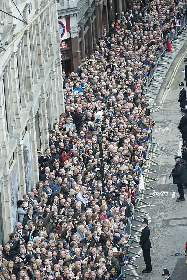 The crowd watches as the coffin bearing the body of former Prime Minister Margaret Thatcher makes it way to St Paul's Cathedral, central London for her funeral service Wednesday April 17, 2013. Margaret Thatcher was laid to rest Wednesday with prayers and ceremony, plus cheers and occasional jeers, as Britain paused to remember a leader who transformed the country _ for the better according to many, but in some eyes for the worse.  (AP Photo/ David Crump, Pool) Photo: David Crump/Daily Mail, Associated Press