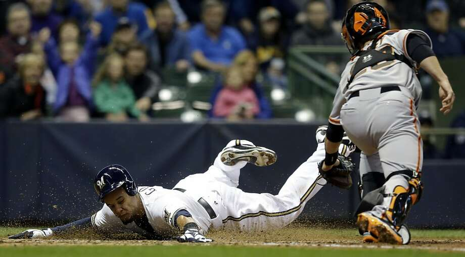 Milwaukee Brewers' Carlos Gomez slides safely past San Francisco Giants catcher Buster Posey during the fifth inning of a baseball game Wednesday, April 17, 2013, in Milwaukee. Gomez scored from third on a sacrifice fly by Yuniesky Betancourt. (AP Photo/Morry Gash) Photo: Morry Gash, Associated Press
