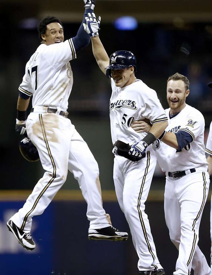 Milwaukee Brewers' Blake Lalli is congratulated by Carlos Gomez (27) and Jonathan Lucroy, right, after hitting a game-winning walk off single during the ninth inning of a baseball game against the San Francisco Giants Wednesday, April 17, 2013, in Milwaukee. The Brewers won 4-3. (AP Photo/Morry Gash) Photo: Morry Gash, Associated Press