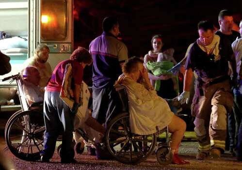 Emergency workers evacuate elderly from a damaged nursing home following an explosion at a fertilizer plant Wednesday, April 17, 2013, in West, Texas. An explosion at a fertilizer plant near Waco caused numerous injuries and sent flames shooting high into the night sky on Wednesday. (AP Photo/ Waco Tribune Herald, Rod Aydelotte) Photo: Rod Aydelotte, Associated Press / Waco Tribune Herald