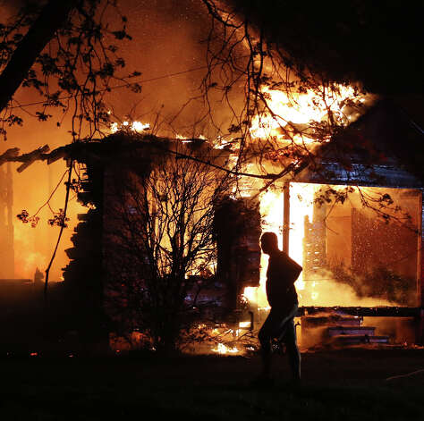 A person looks on as emergency workers fight a house fire after a nearby fertilizer plant exploded Wednesday, April 17, 2013, in West, Texas. (AP Photo/Waco Tribune Herald, Rod Aydelotte) Photo: Rod Aydelotte, Associated Press / Waco Tribune Herald