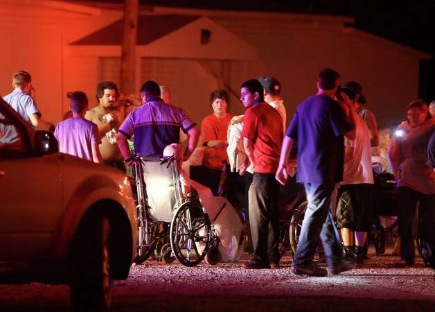 Elderly persons from a nearby nursing home are triaged in a parking lot before being moved to a school stadium following a fertilizer plant explosion Wednesday, April 17, 2013, in West, Texas. The explosion near Waco Wednesday night injured dozens of people and sent flames shooting high into the night sky, leaving the factory a smoldering ruin and causing major damage to surrounding buildings. (AP Photo/Waco Tribune Herald, Rod Aydelotte) Photo: Rod Aydelotte, Associated Press / Waco Tribune Herald