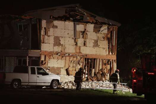 Rescue workers pass a damaged apartment complex after a nearby fertilizer plant exploded Wednesday, April 17, 2013, in West, Texas. (AP Photo/ Waco Tribune Herald, Rod Aydelotte) Photo: Rod Aydelotte, Associated Press / Waco Tribune Herald