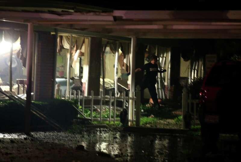 An emergency worker walks through damaged apartment building following a fertilizer plant explosion