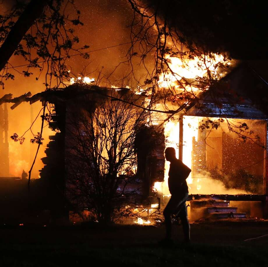 A person looks on as emergency workers fight a house fire after the blast. (AP Photo/Waco Tribune Herald, Rod Aydelotte)