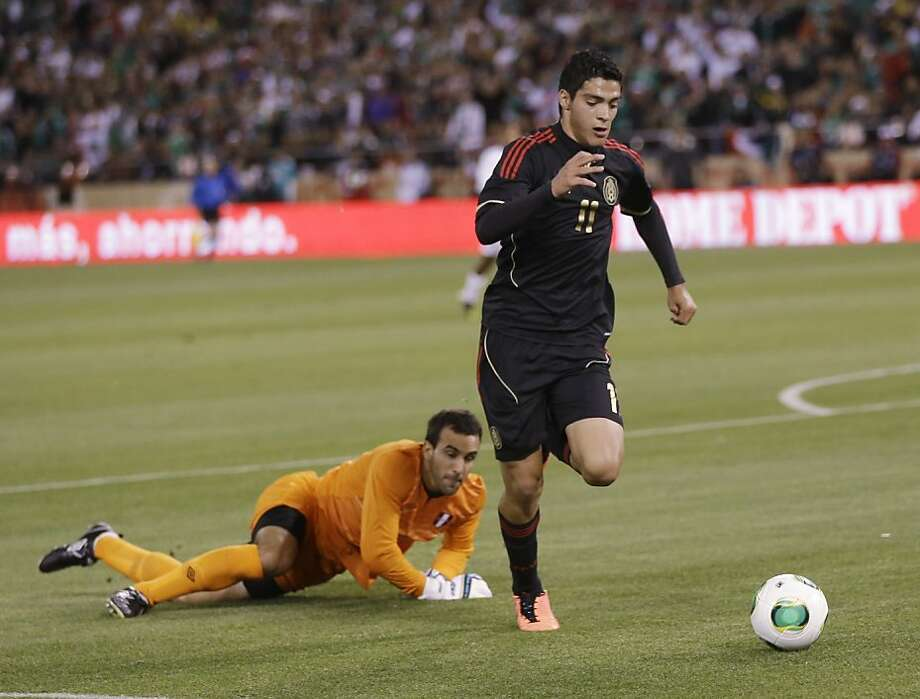 Mexico's Raul Jimenez (11) dribbles past Peru goalkeeper Jose Carvallo, left, during the first half of an international friendly soccer match on Wednesday, April 17, 2013, in San Francisco. (AP Photo/Marcio Jose Sanchez) Photo: Marcio Jose Sanchez, Associated Press