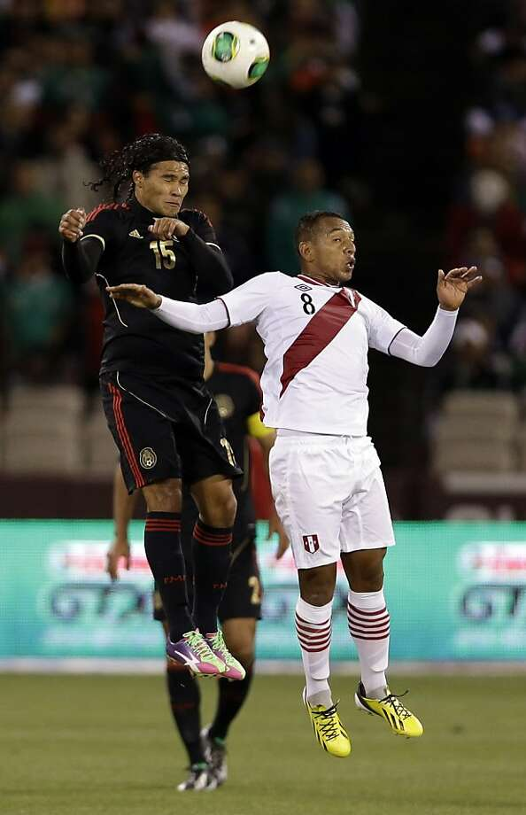 Mexico's Carlos Peña, left, battles for a header next to Peru's Michael Guevara (8) during the first half of an international friendly soccer match on Wednesday, April 17, 2013, in San Francisco. (AP Photo/Marcio Jose Sanchez) Photo: Marcio Jose Sanchez, Associated Press