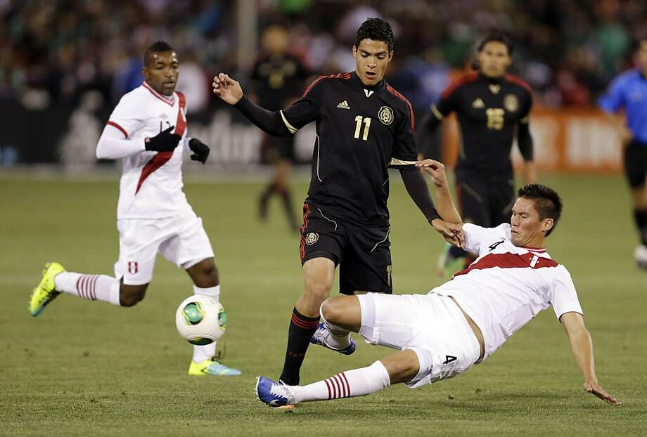 Peru's Orlando Contreras, right, makes a slide tackle on Mexico's Raul Jimenez during the first half of an international friendly soccer match on Wednesday, April 17, 2013, in San Francisco. (AP Photo/Marcio Jose Sanchez) Photo: Marcio Jose Sanchez, Associated Press