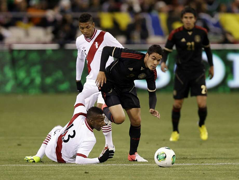 Mexico's Pablo Barrera, center, dribbles past Peru's Jair Cespedes (13) during the first half of an international friendly soccer match on Wednesday, April 17, 2013, in San Francisco. (AP Photo/Marcio Jose Sanchez) Photo: Marcio Jose Sanchez, Associated Press