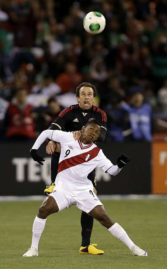 Mexico's Gerardo Torrado, top, defends on Peru's Yordy Reyna during the first half of an international friendly soccer match on Wednesday, April 17, 2013, in San Francisco. (AP Photo/Marcio Jose Sanchez) Photo: Marcio Jose Sanchez, Associated Press