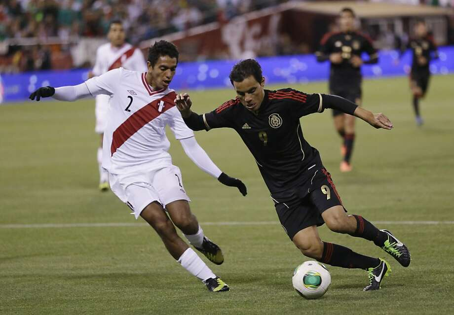 Mexico's Omar Bravo (9) is defended by Peru's Nestor Duarte during the second half of an international friendly soccer match on Wednesday, April 17, 2013, in San Francisco. The match ended in a 0-0 tie.(AP Photo/Marcio Jose Sanchez) Photo: Marcio Jose Sanchez, Associated Press