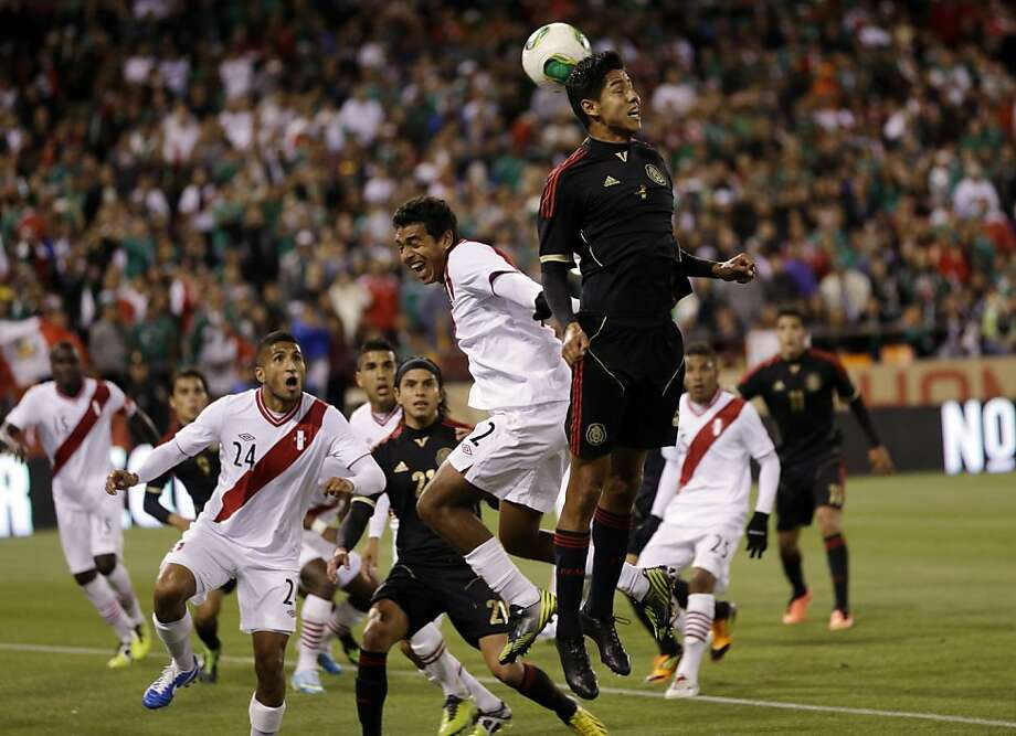 Mexico's Hugo Ayala, center, heads the ball back to the goal on a corner kick next to Peru's Nestor Duarte (2), during the second half of an international friendly soccer match on Wednesday, April 17, 2013, in San Francisco. The match ended in a 0-0 tie.(AP Photo/Marcio Jose Sanchez) Photo: Marcio Jose Sanchez, Associated Press
