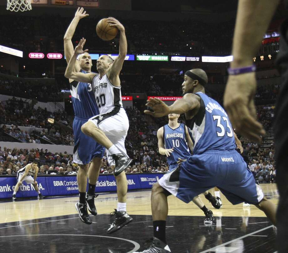 The Spurs\' Manu Ginobili (20) drives to the basket against the Minnesota Timberwolves\' Greg Stiemsma (34) in the first quarter at the AT&T Center on Wednesday, April 17, 2013.
