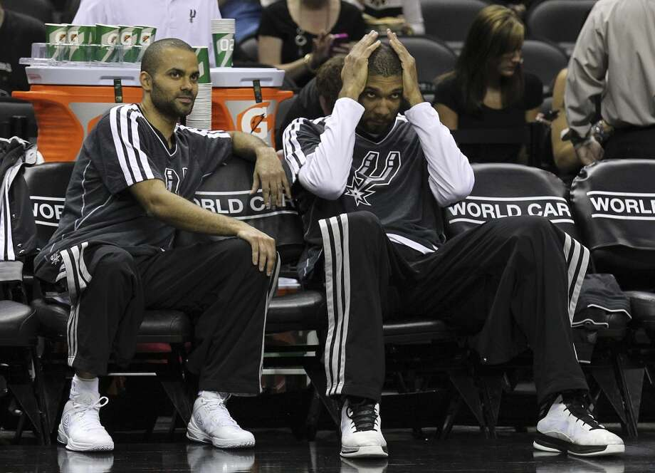 The Spurs\' Tony Parker (09) and Tim Duncan (21) relax on the bench before the game against the Minnesota Timberwolves at the AT&T Center on Wednesday, April 17, 2013.