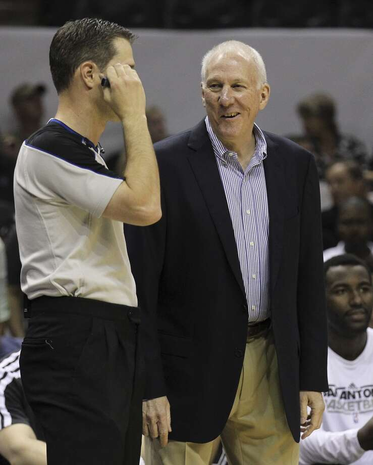 Spurs coach Gregg Popovich chats with a game official during the game against the Minnesota Timberwolves in the first quarter at the AT&T Center on Wednesday, April 17, 2013.
