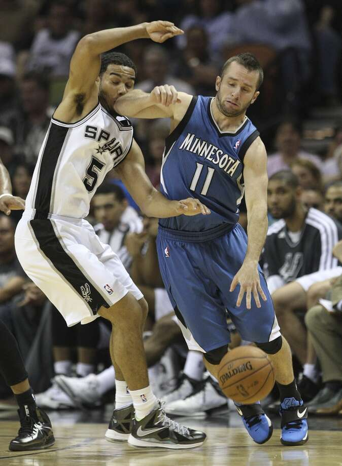 The Spurs\' Cory Joseph (05) gets an elbow to the face from the Minnesota Timberwolves\' Jose Barea (11) in the second half at the AT&T Center on Wednesday, April 17, 2013. Timberwolves defeated the Spurs, 108-95.