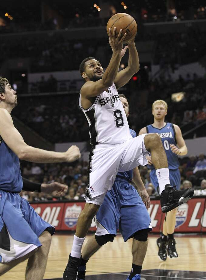 The Spurs\' Patty Mills (08) drives the lane against the Minnesota Timberwolves\' Jose Barea (11) and Alexey Shved (01) in the second half at the AT&T Center on Wednesday, April 17, 2013. Timberwolves defeated the Spurs, 108-95.