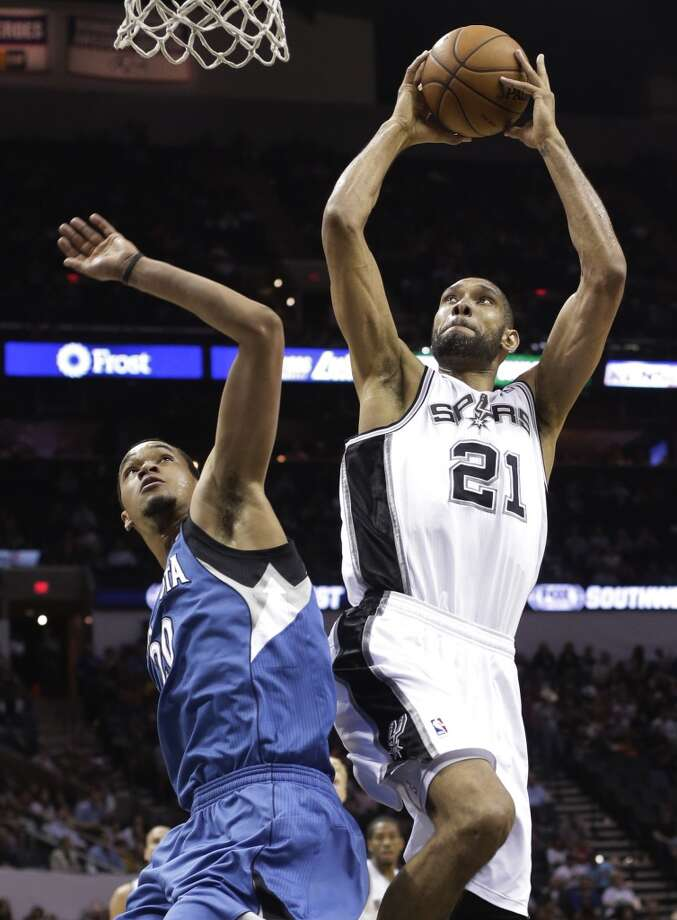 The Spurs\' Tim Duncan (21) shoots over the Minnesota Timberwolves\' Chris Johnson (20) during the first half on Wednesday, April 17, 2013, at the AT&T Center.