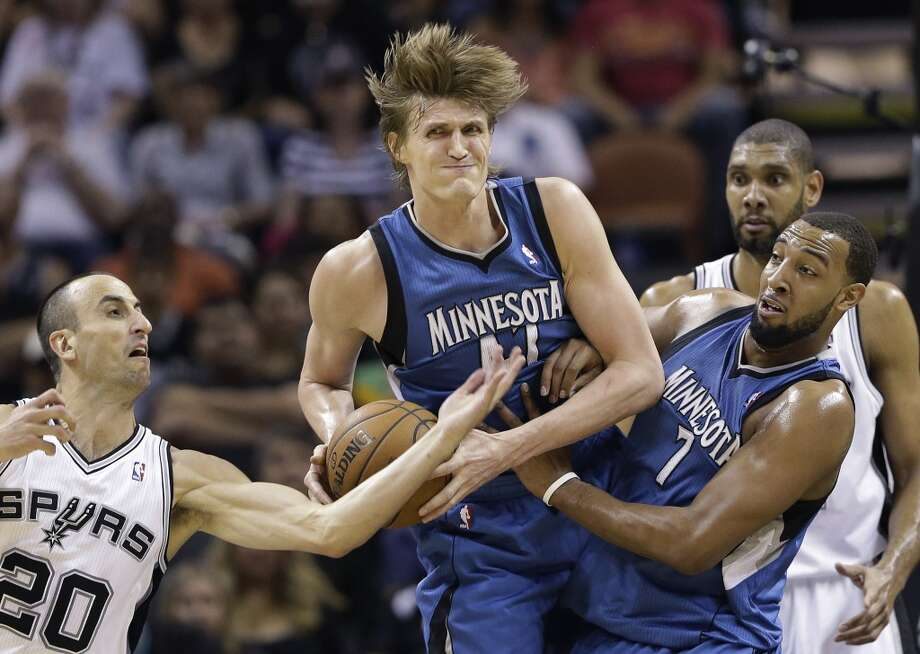 The Minnesota Timberwolves\' Andrei Kirilenko (center) and teammate Derrick Williams (7) pull down a rebound as the Spurs\' Manu Ginobili (20), reaches in during the first half on Wednesday, April 17, 2013, at the AT&T Center.