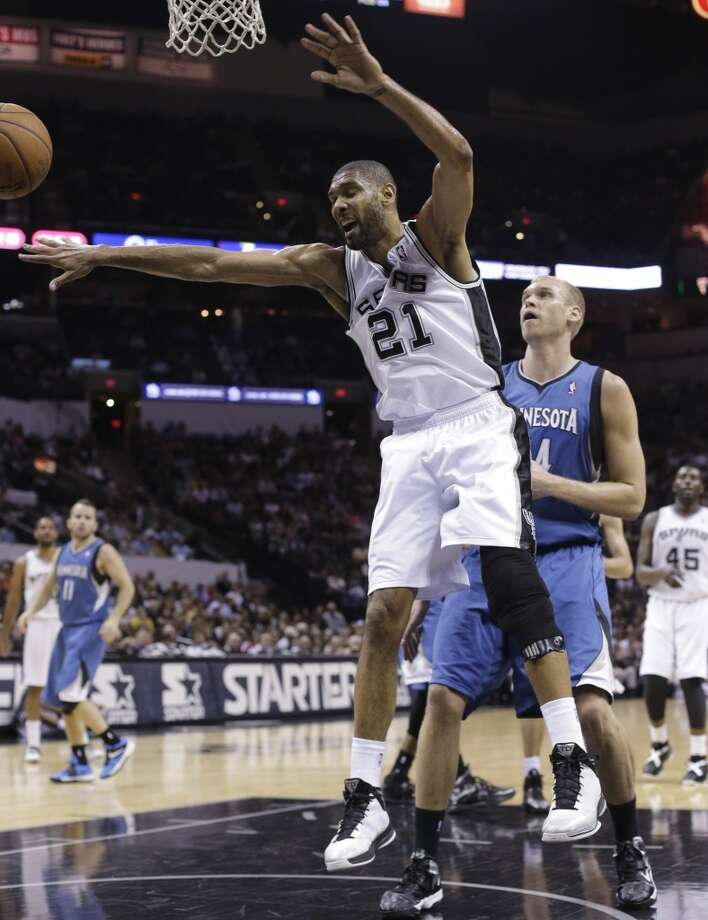 The Spurs\' Tim Duncan (21) loses control of the ball as the Minnesota Timberwolves\' Greg Stiemsma (right) defends him during the first half on Wednesday, April 17, 2013, at the AT&T Center.
