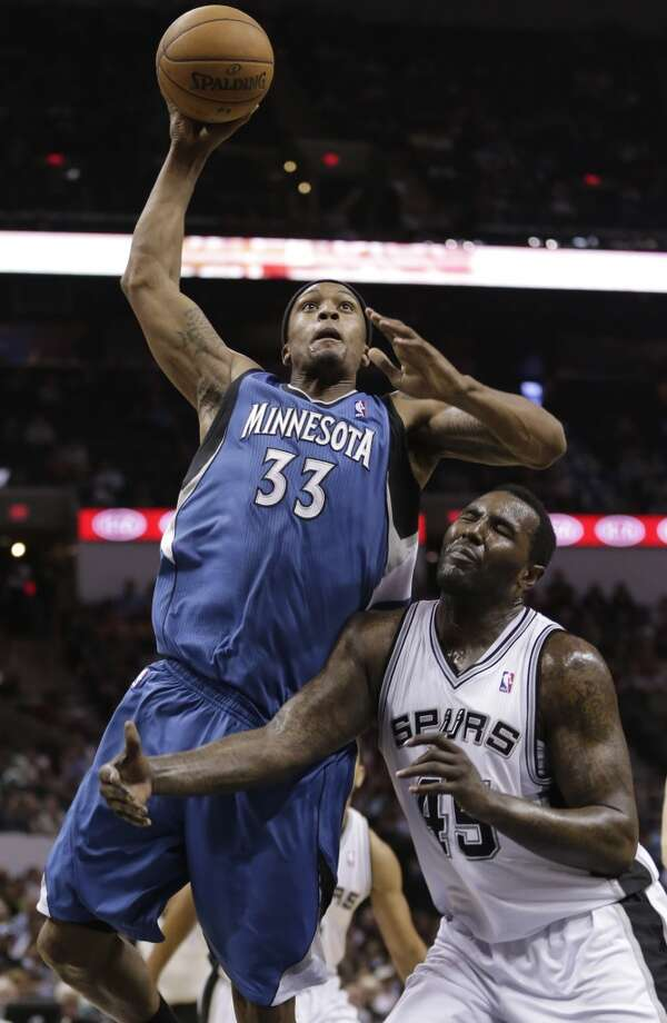 The Minnesota Timberwolves\' Dante Cunningham (33) is fouled by the Spurs\' DeJuan Blair (right) while shooting during the second half on Wednesday, April 17, 2013,at the AT&T Center. Minnesota won 108-95.