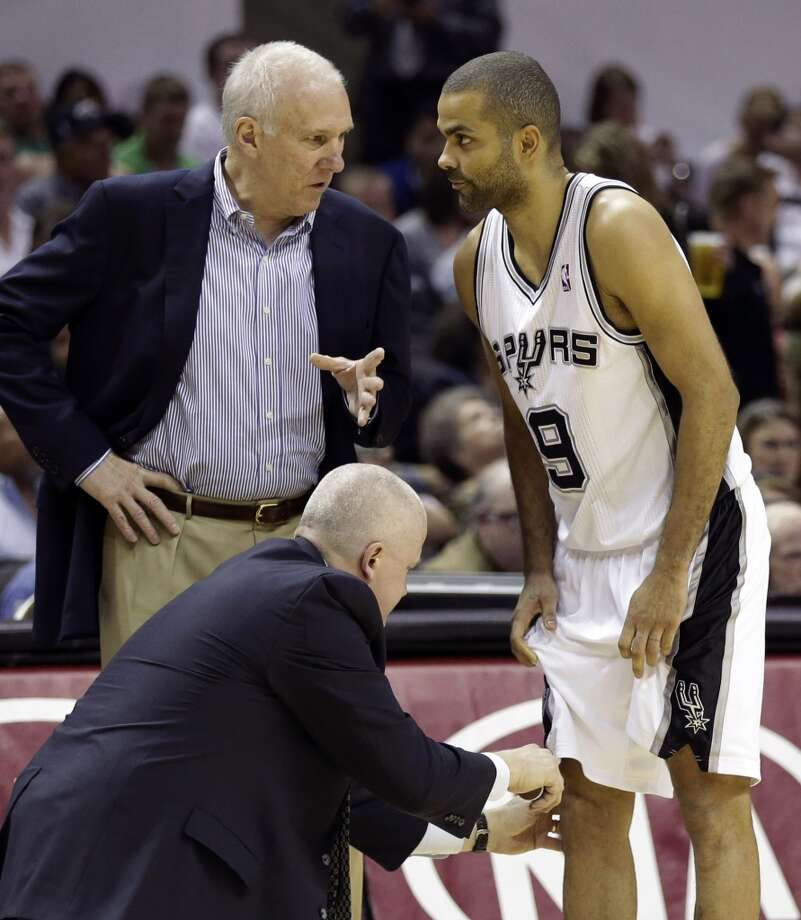 The Spurs\' Tony Parker (9) talks with coach Gregg Popovich as a trainer tends to his knee during the second half against the Minnesota Timberwolves on Wednesday, April 17, 2013, at the AT&T Center. Minnesota won 108-95.