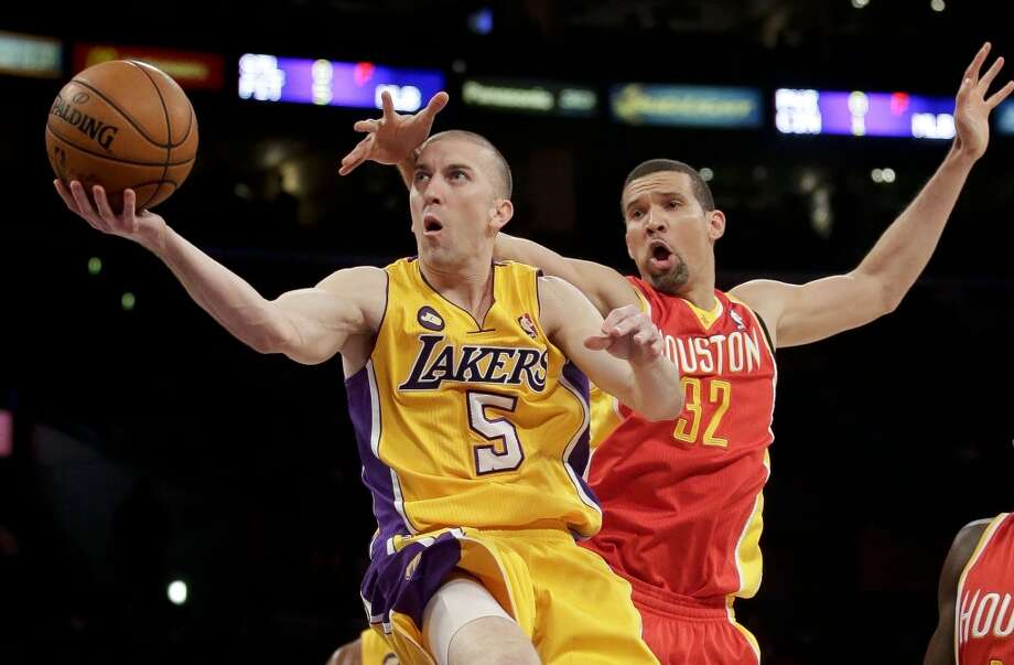 Steve Blake of the Lakers has a hand put in his face by Francisco Garcia of the Rockets. Photo: Wally Sklaij, Los Angeles Times/MCT