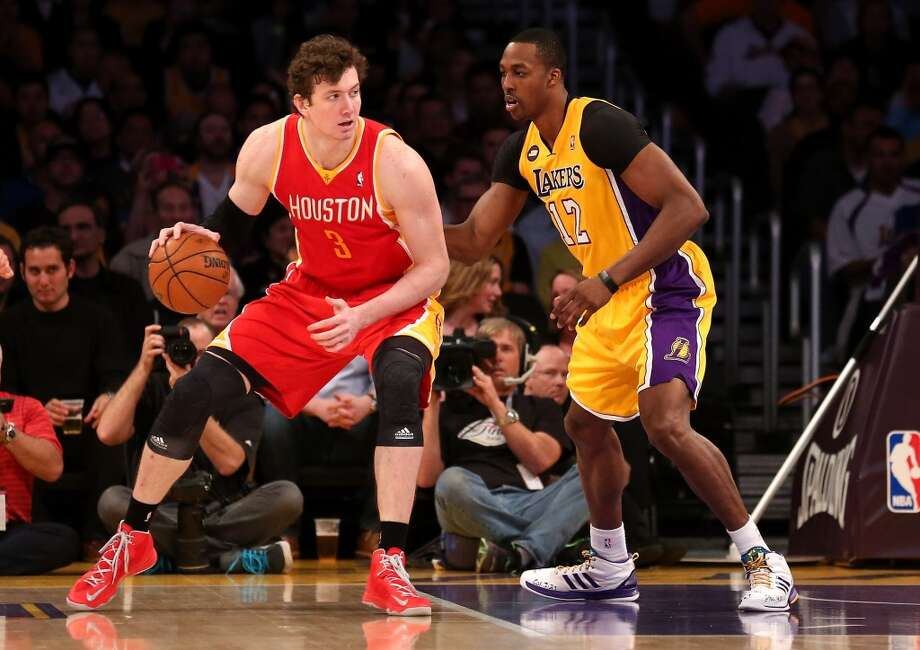 Rockets center Omer Asik backs down Dwight Howard of the Lakers.